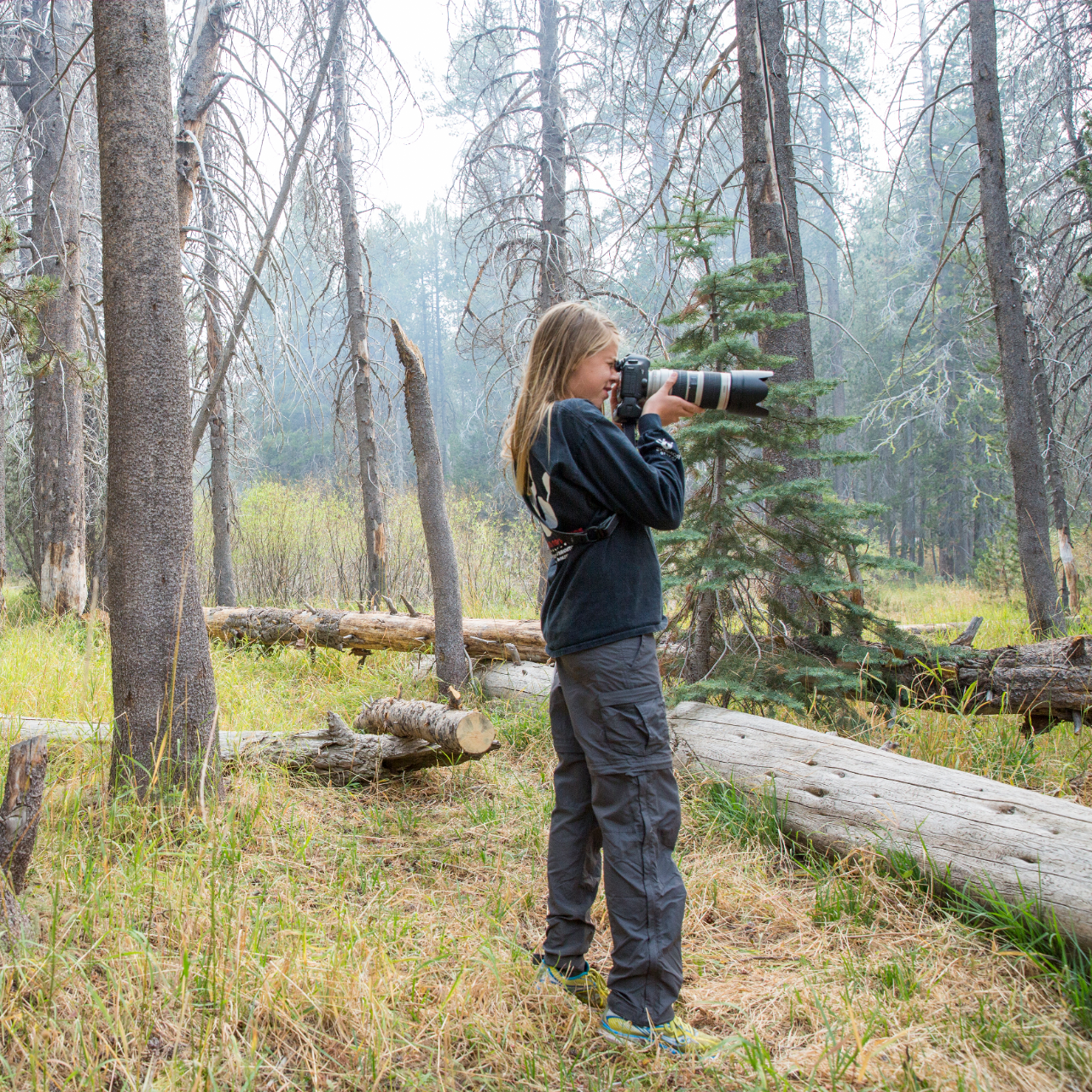 Girl standing in forest taking photo with large camera
