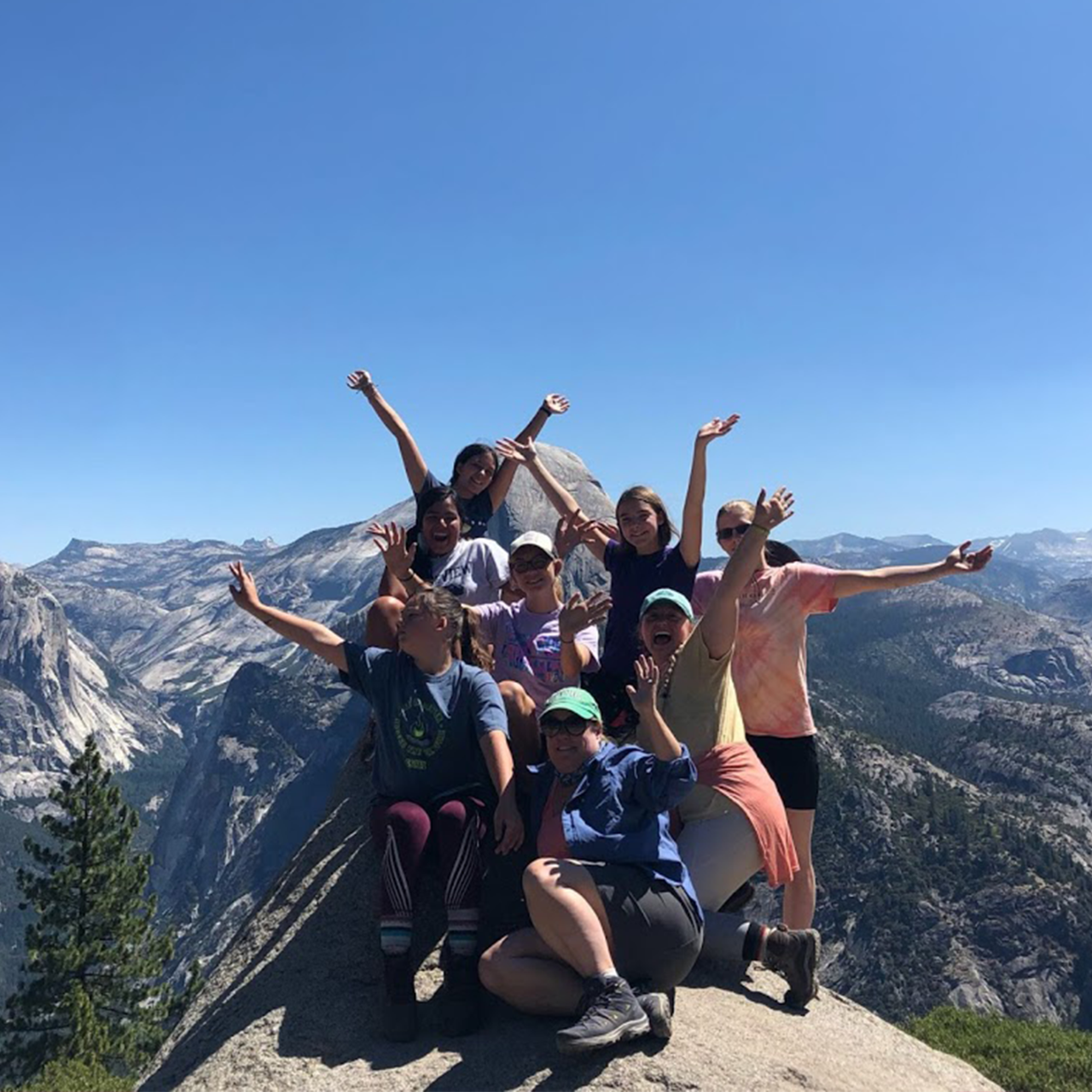 Group of girls standing on top of mountain, posing with hands raised