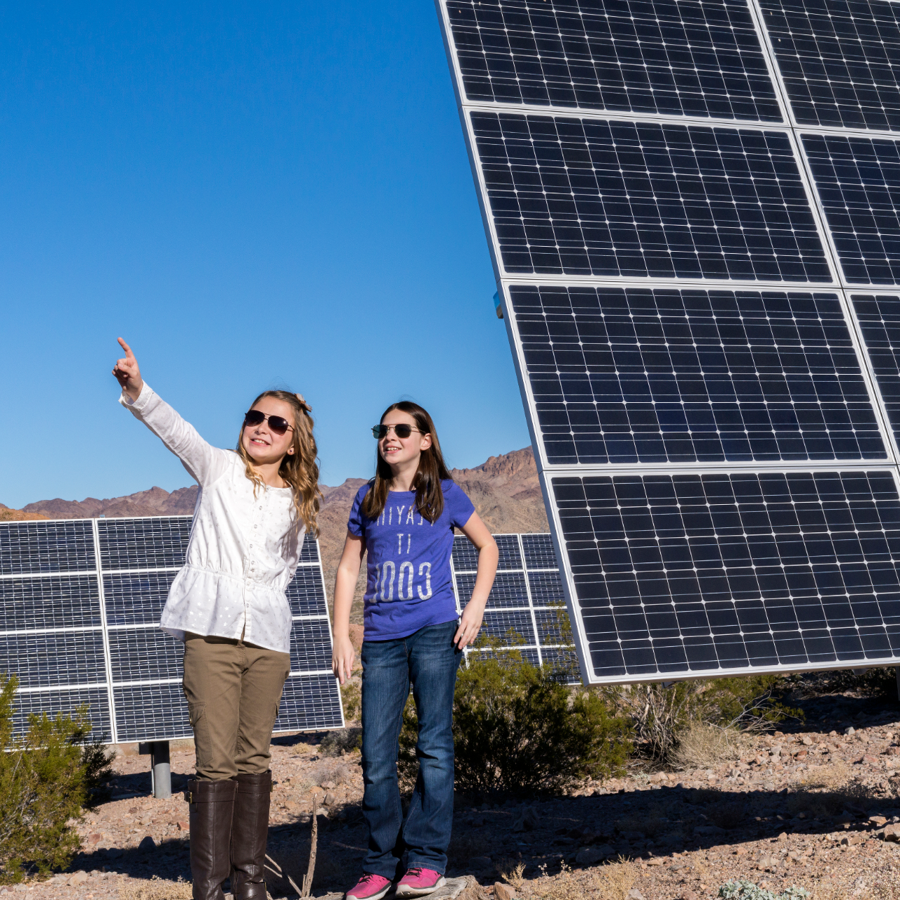 Two girls in a field of solar powering panels