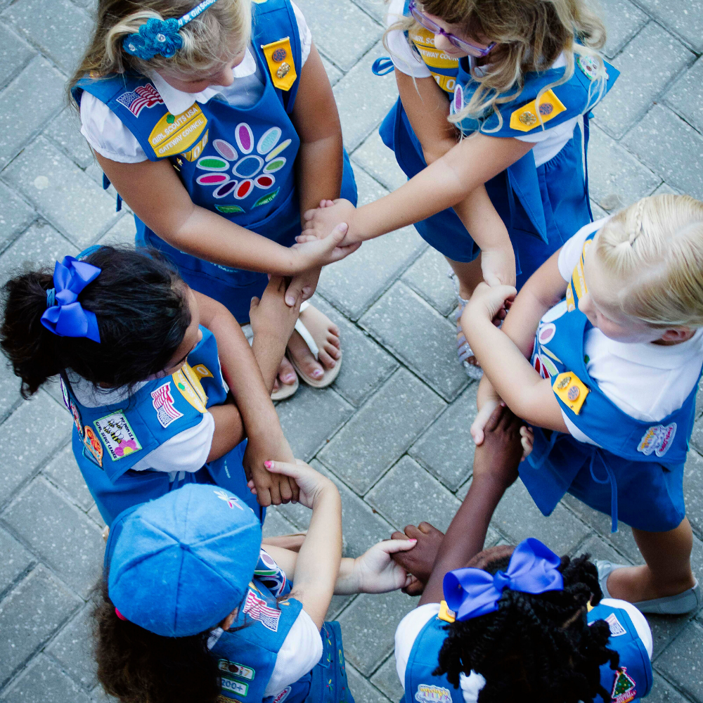 Group of Girl Scout Daisies in uniform, standing in a circle, linking arms, making the Girl Scout friendship circle