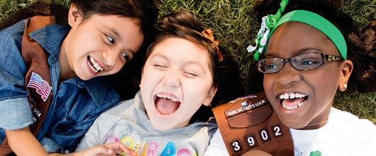 3 Brownies lying in the grass, laughing